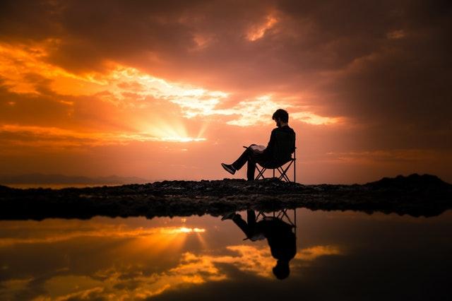 Man is aan het lezen met mooie lucht op achtergrond